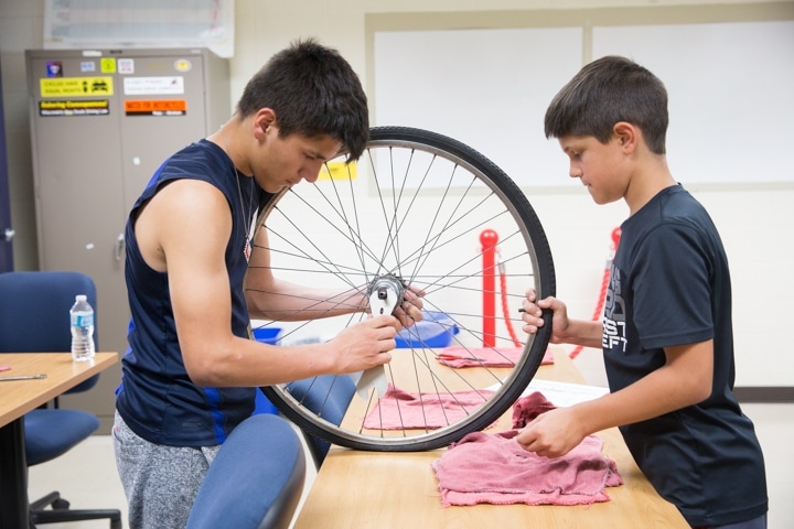 Boys use wrench to assemble bike tire at Moraine Park Tech Knowledge College