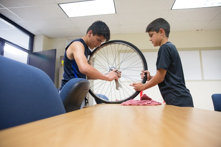 Two boys work on bike tire during Moraine Park TKC summer camp
