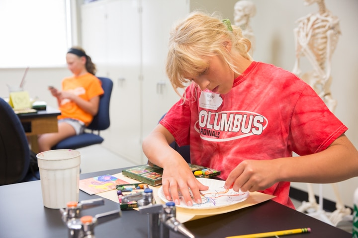 Girl works on painting project during art activity at Moraine Park Tech Knowledge College