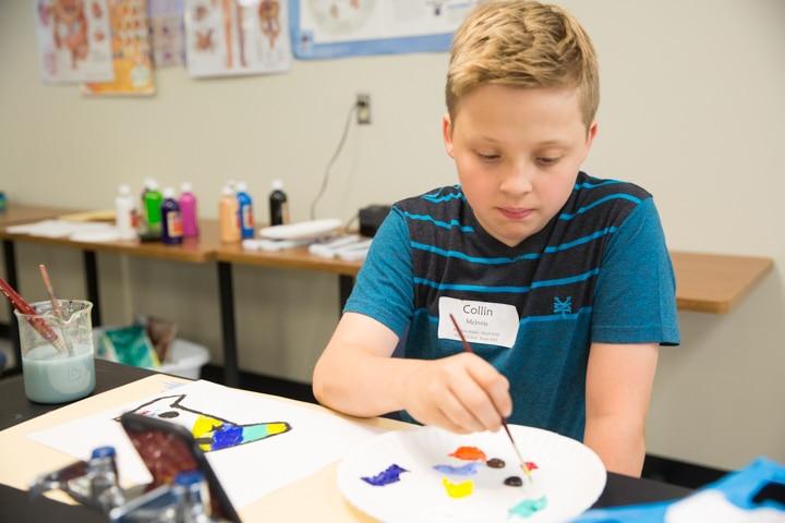 Boy paints during art activity at Moraine Park Tech Knowledge College