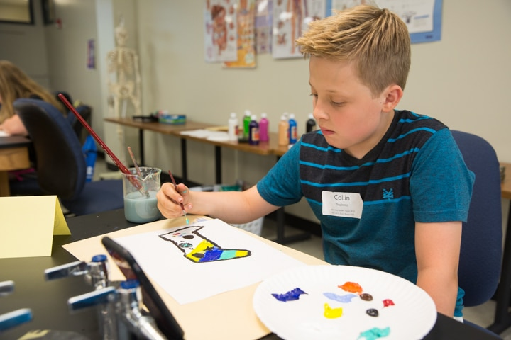 Boy paints during art activity at Moraine Park Tech Knowledge College