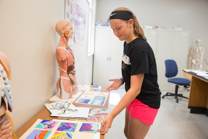 Girl places finished art project on table at Moraine Park TKC summer camp