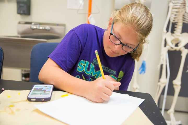 Girl sketches with paper and pencil during Moraine Park Tech Knowledge College art activity