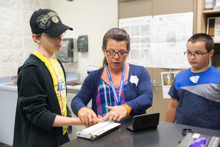 Instructor Joan Barfield demonstrates fingerprinting with paper and ink during criminal justice activity at Moraine Park TKC
