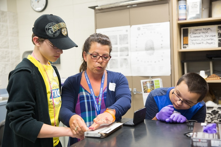 Instructor Joan Barfield demonstrates fingerprinting activity during criminal justice course at Moraine Park summer camp