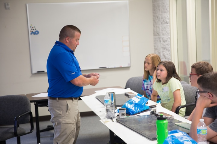 Male instructor discusses dusting for fingerprints in criminal justice course at Moraine Park TKC summer camp
