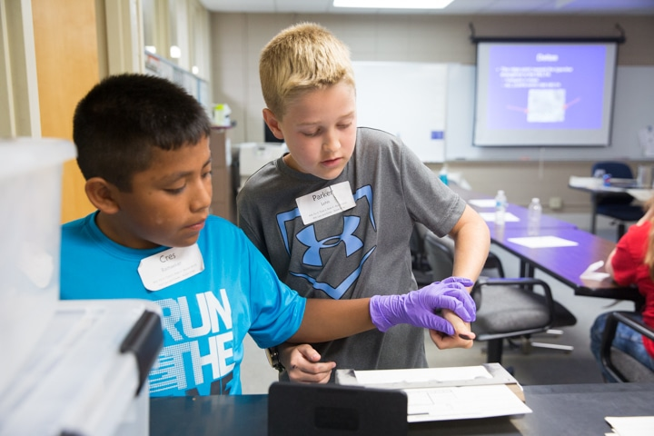 Boys do fingerprint activity with paper and ink at Moraine Park Tech Knowledge College