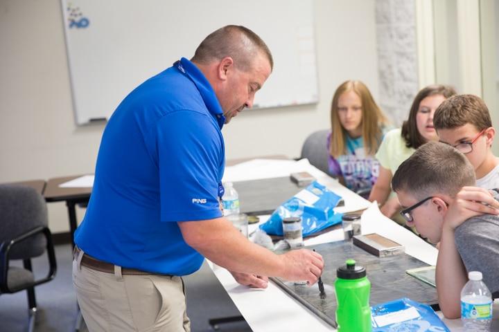 Male instructor demonstrates dusting for fingerprints