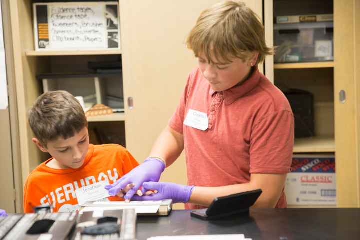 Boys use paper and ink to take fingerprints of each other at Moraine Park TKC