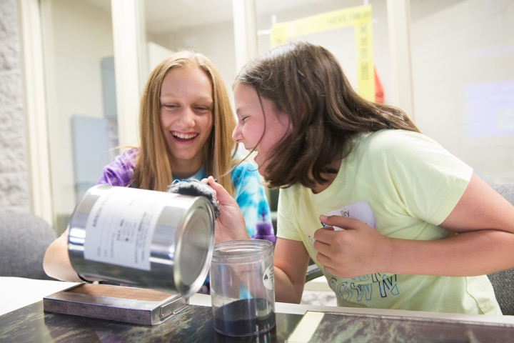 Two girls laugh while dusting for fingerprints on large can at Moraine Park TKC