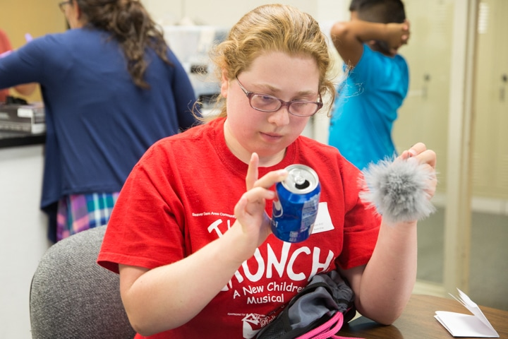 Girl inspects soda can for fingerprints during Moraine Park TKC criminal justice activity