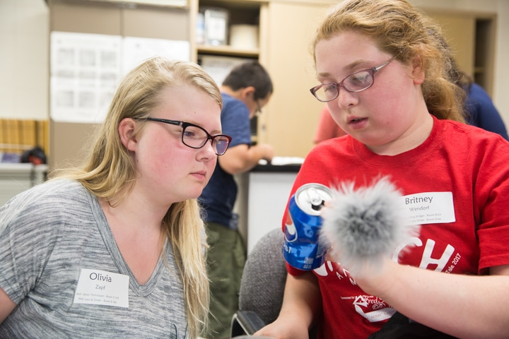 Two girls inspect soda can for fingerprints during Moraine Park TKC criminal justice activity
