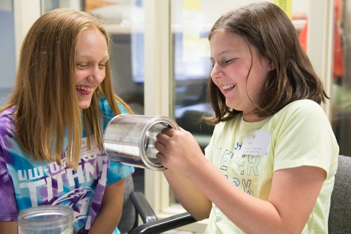 Two girls laugh while looking for fingerprints on can during Moraine Park TKC summer camp