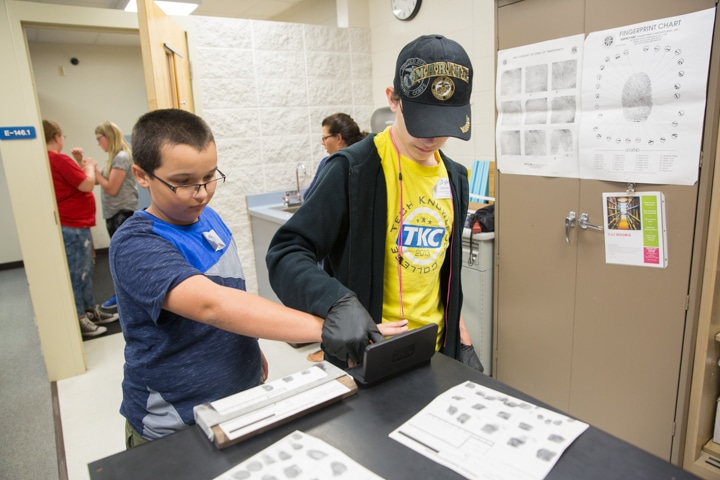 Two boys make fingerprints in Moraine Park TKC criminal justice activity