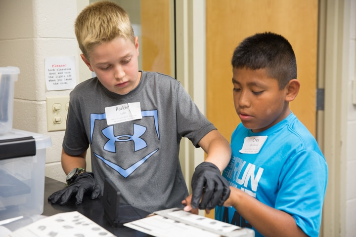 Two boys use ink and paper to take fingerprints in Moraine Park TKC criminal justice activity