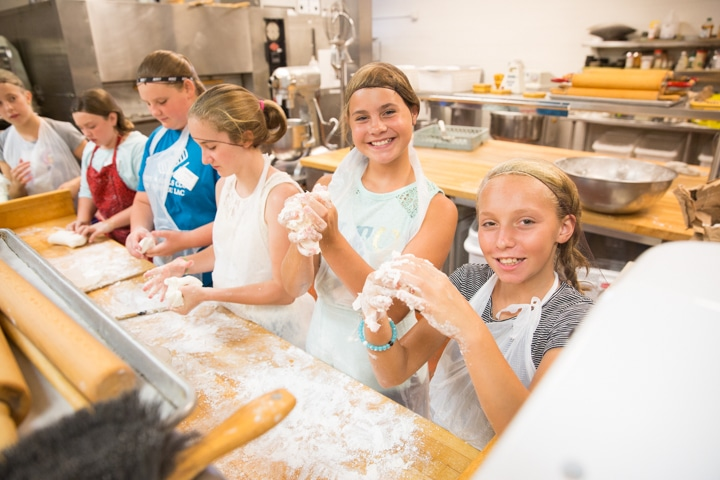 Girls hold up dough and smile during culinary activity at Moraine Park TKC summer camp
