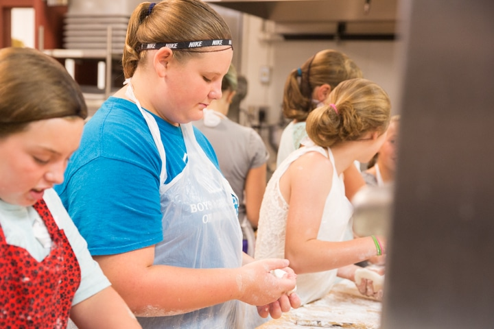Girl holds dough in hands in kitchen at Moraine Park TKC