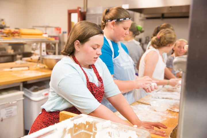 Girl works with dough in kitchen at Moraine Park TKC summer camp