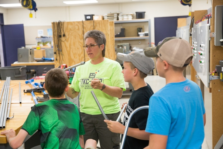 Female electricity instructor holds piping and talks to class of young students