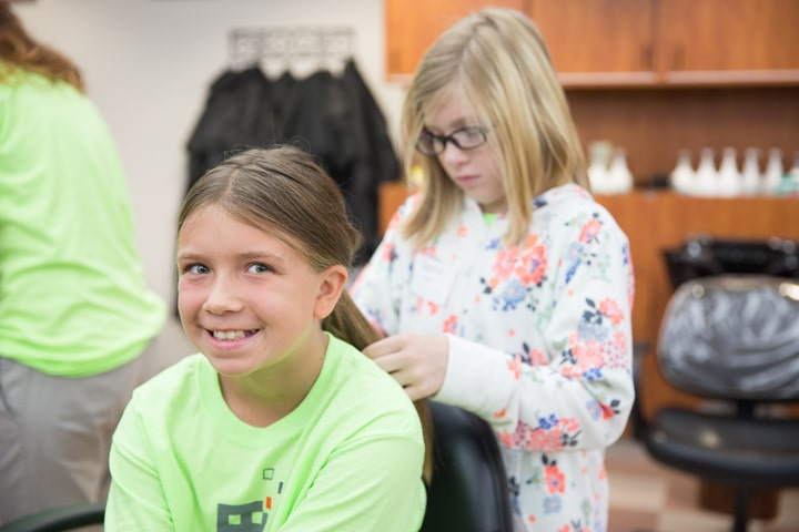 Girls style hair and smile during Moraine Park Tech Knowledge College