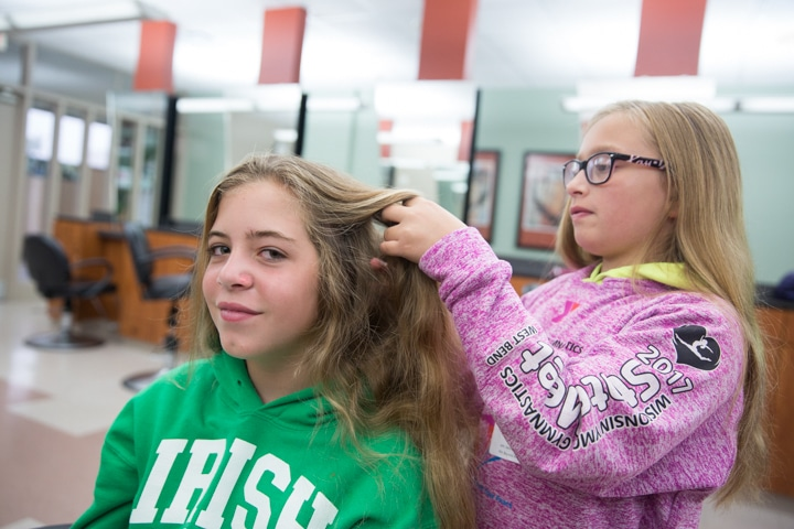 Girls style hair during Moraine Park Tech Knowledge College