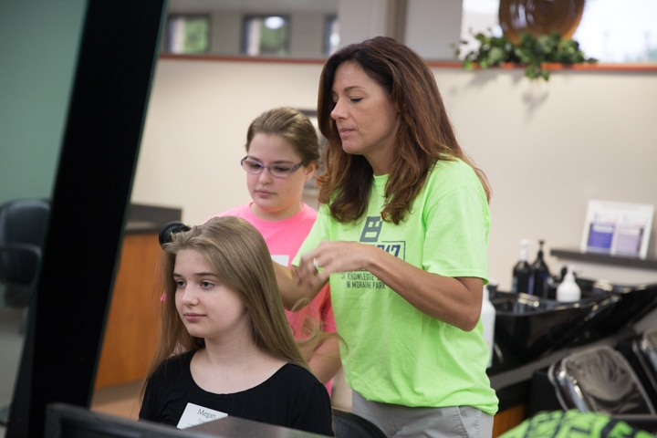 Instructor shows young girls hair styling techniques during TKC summer camp cosmetology activity