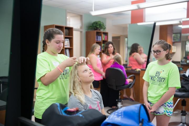 Girls work on braiding hair during TKC summer camp cosmetology activity