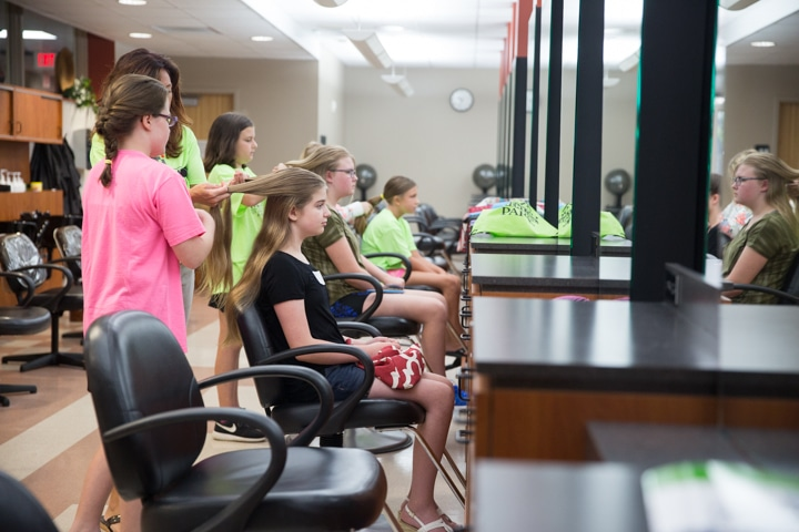 Girls work on braiding hair during TKC summer camp cosmetology activity