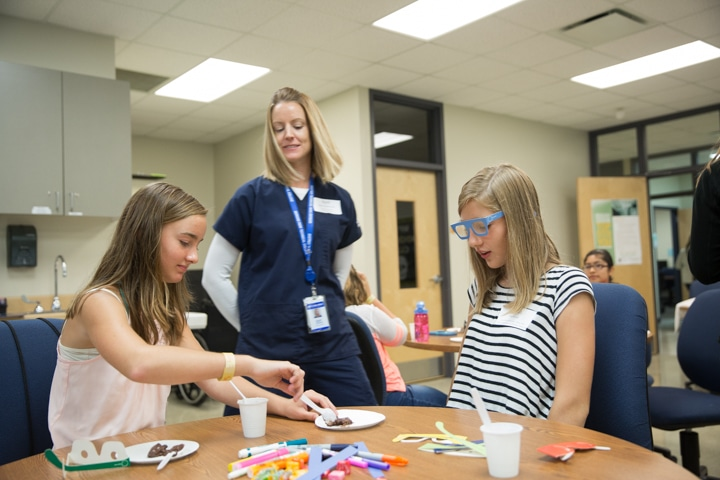 Girls feed pudding with spoons during health activity at Moraine Park