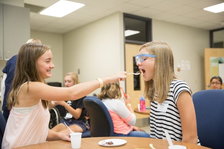 Girls feed pudding with spoons to each other during health activity at Moraine Park