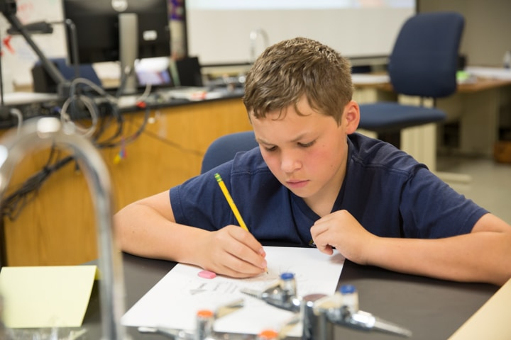 Boys draws with pencil during art activity at Moraine Park Tech Knowledge College