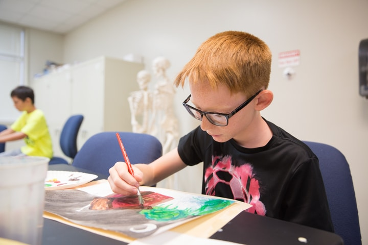Boy works on painting activity during Moraine Park Tech Knowledge College