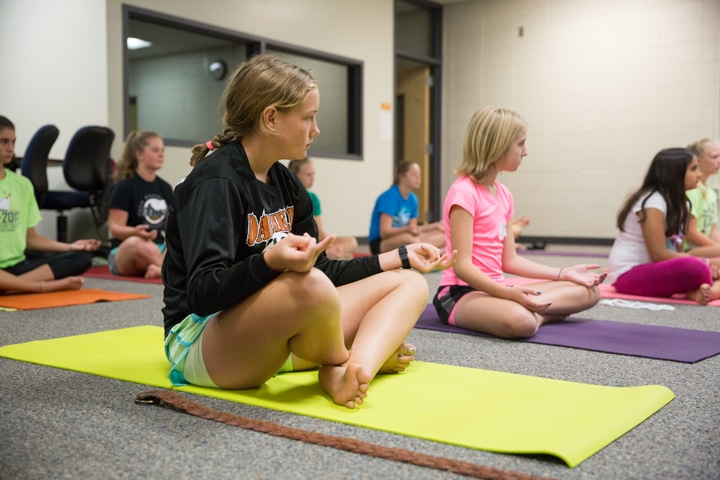 Girls practice yoga on mats at Moraine Park