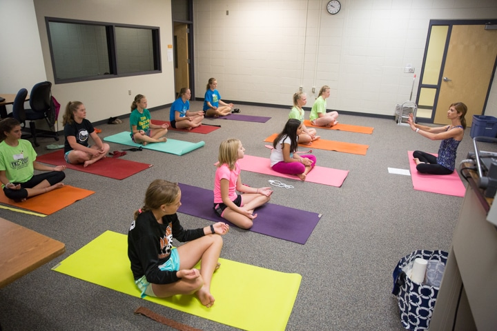 Classroom of girls practice yoga pose at Moraine Park TKC summer camp