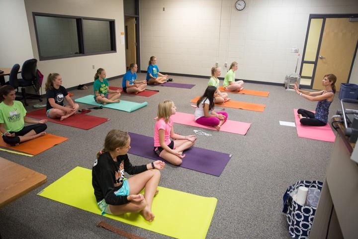 Classroom of girls practice yoga pose at Moraine Park TKC summer camp