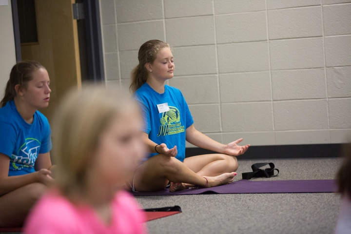Girl practices yoga pose with eyes closed at Moraine Park TKC
