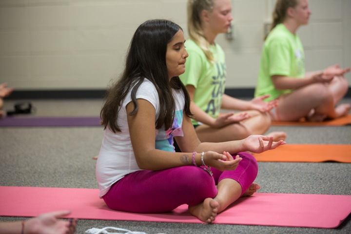 Girl closes eyes and practices yoga pose at Moraine Park TKC