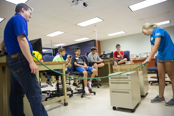 Student use hose and water to test bridge strength during TKC engineering activity
