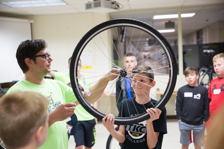 Student holds wheel as instructor talks about bike tires at Moraine Park Tech Knowledge College