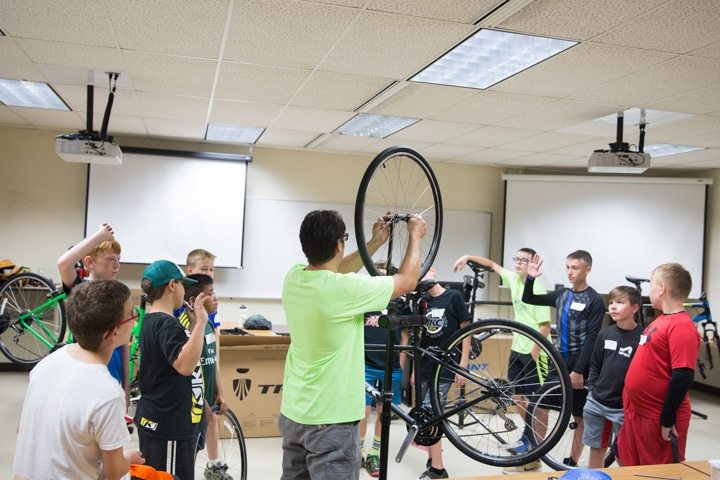 Instructor shows bike tires to classroom of youth