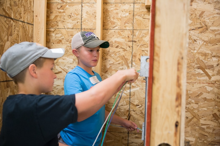 Youth feed wires during electrical activity at TKC in Fond du Lac