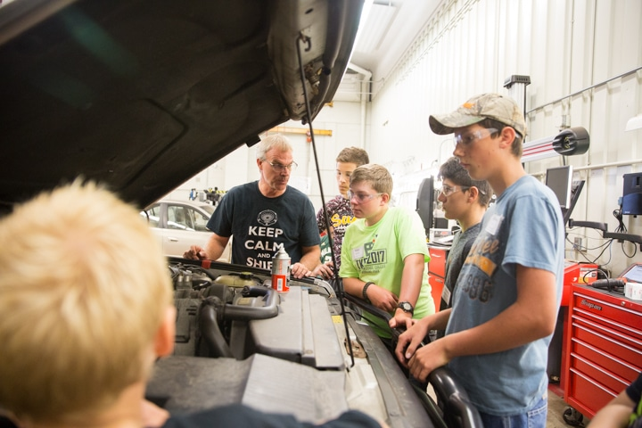 Students look under hood of car at Tech Knowledge College in Fond du Lac