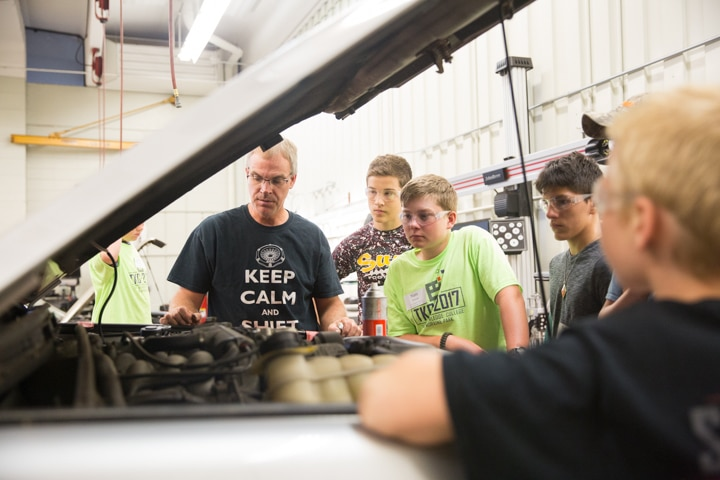 Students look under hood of car during Moraine Park TKC event