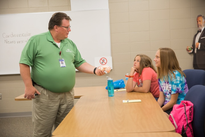 EMT instructor shows simulated body parts to smiling students at Moraine Park TKC summer camp