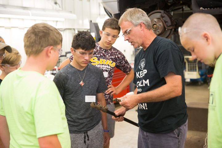 Automotive instructor works with youth during Moraine Park TKC summer camp