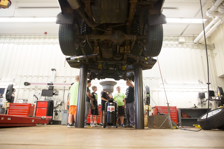 Youth learn how to change oil in car during Moraine Park automotive activity