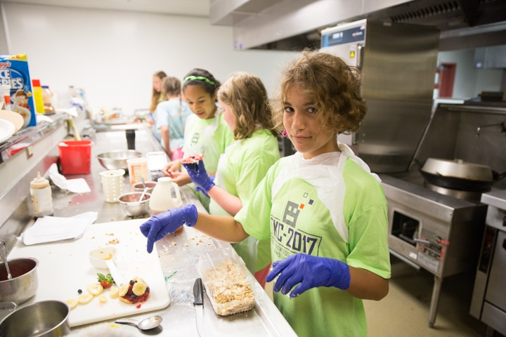 Girl points to food in Moraine Park kitchen