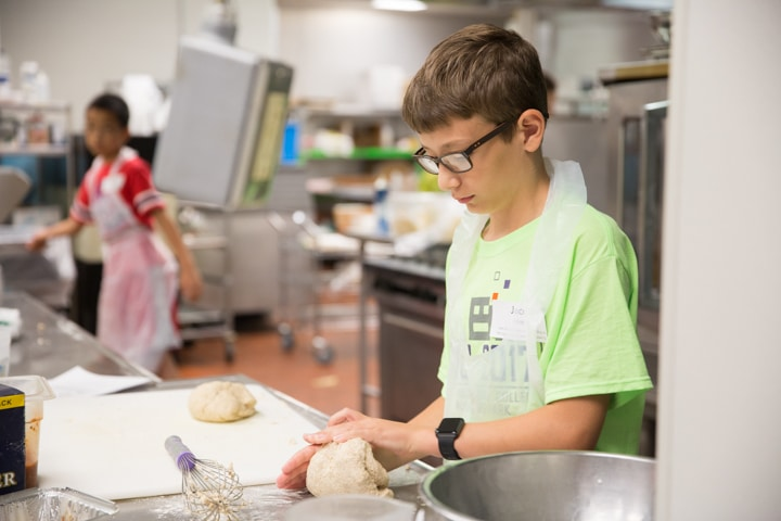 Boy works with dough in kitchen at Moraine Park