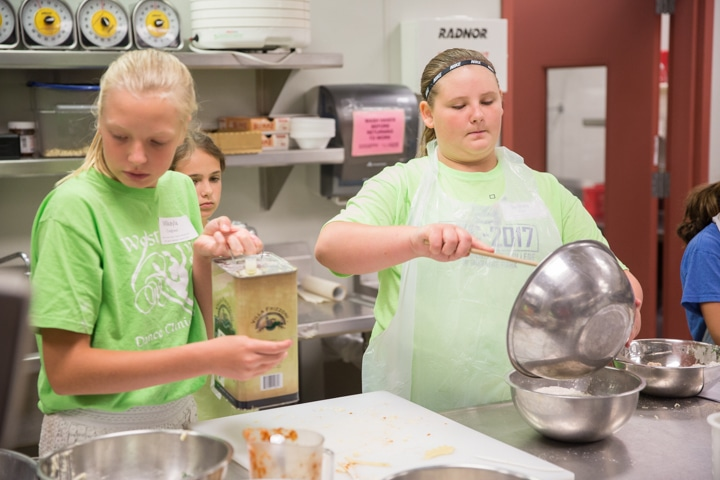Girls work in kitchen at Moraine Park TKC event