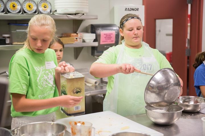 Girls work in kitchen at Moraine Park TKC event